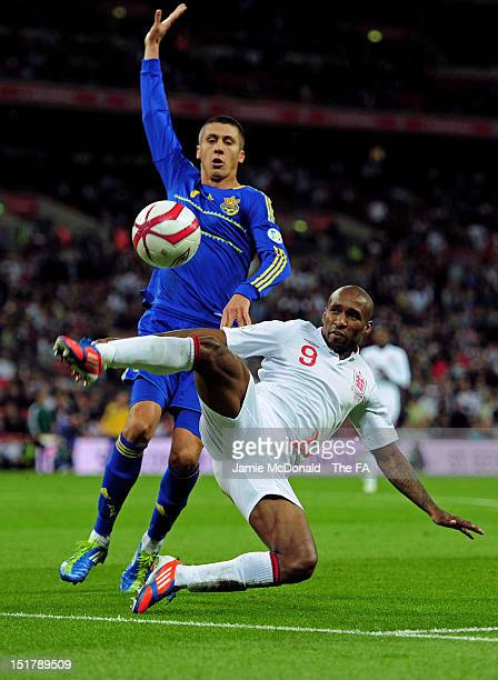 Jermain Defoe of England tries to keep the ball in watched by Yevgen Khacheridi of Ukraine during the FIFA 2014 World Cup qualifier group H match...