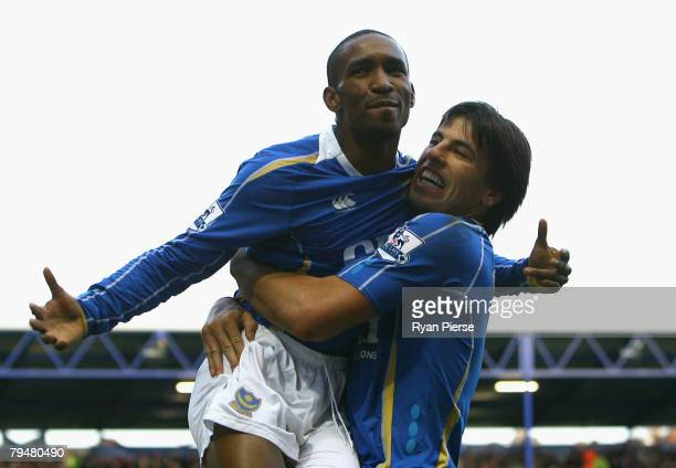 Jermain Defoe of Portsmouth celebrates with teammate Milan Baros after scoring his teams first goal during the Barclays Premier League match between...