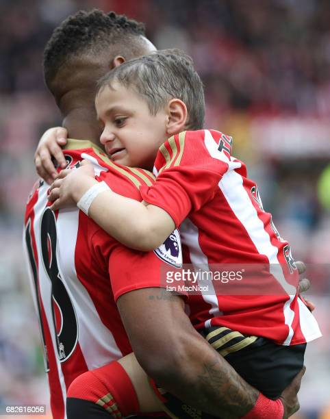 Jermain Defoe of Sunderland and Bradley Lowery are seen walking out prior to the Premier League match between Sunderland and Swansea City at Stadium...