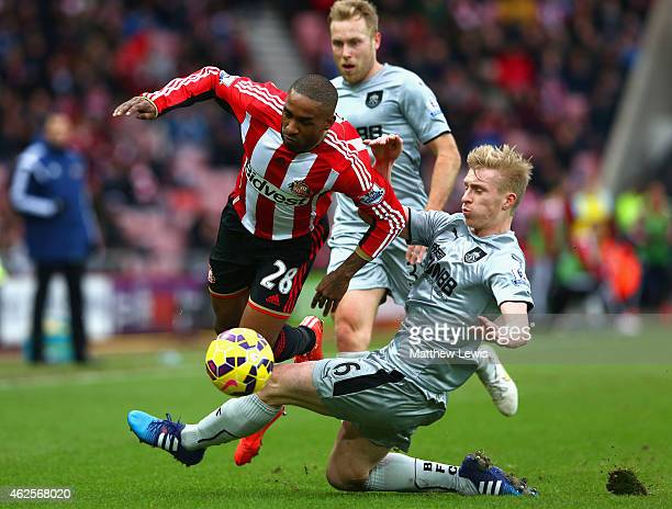 Jermain Defoe of Sunderland is tackled by Ben Mee of Burnley during the Barclays Premier League match between Sunderland and Burnley at Stadium of...