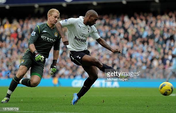 Jermain Defoe of Tottenham Hotspur beats Joe Hart of Manchester City to score his team's first goal during the Barclays Premier League match between...
