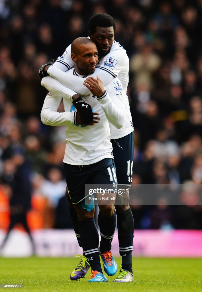 Jermain Defoe (front) of Tottenham Hotspur is embraced by his team mate Emmanuel Adebayor at the end of his final home game following the Barclays Premier League match between Tottenham Hotspur and Everton at White Hart Lane on February 9, 2014 in London, England.