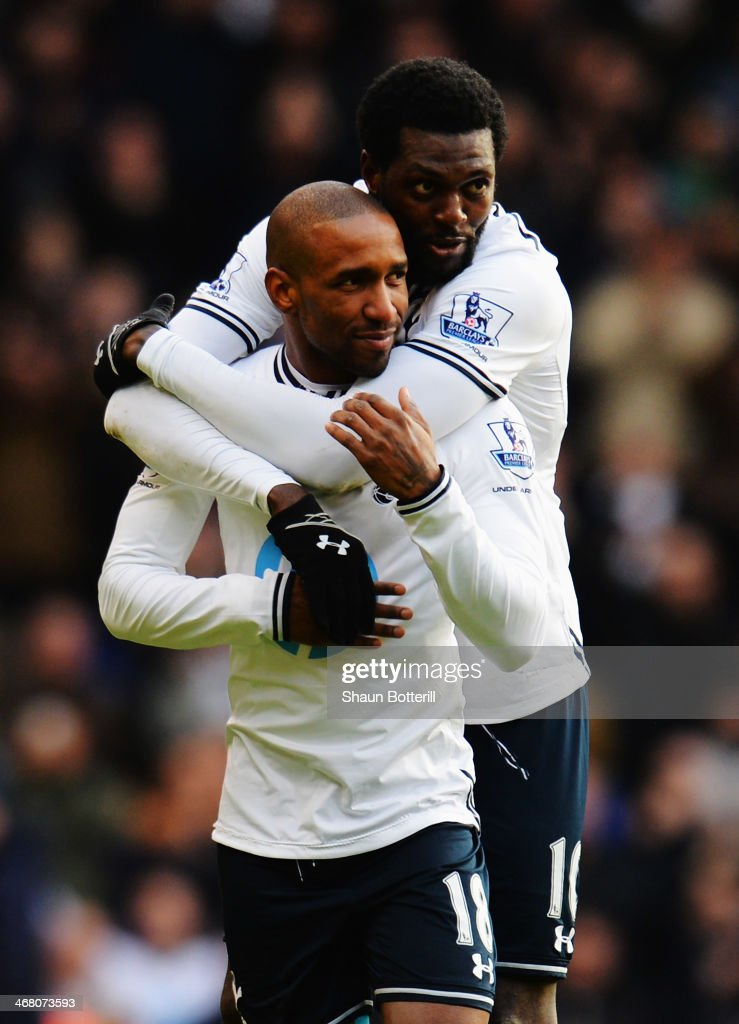 Jermain Defoe (front) of Tottenham Hotspur is embraced by his team mate Emmanuel Adebayor at the end of his final home game before joining Toronto FC following the Barclays Premier League match between Tottenham Hotspur and Everton at White Hart Lane on February 9, 2014 in London, England.