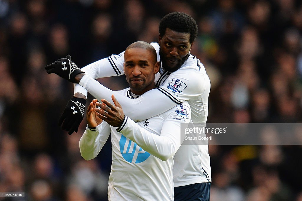 Jermain Defoe (L) of Tottenham Hotspur is embraced by his team mate Emmanuel Adebayor (R) at the end of his final home game before joining Toronto FC following the Barclays Premier League match between Tottenham Hotspur and Everton at White Hart Lane on February 9, 2014 in London, England.