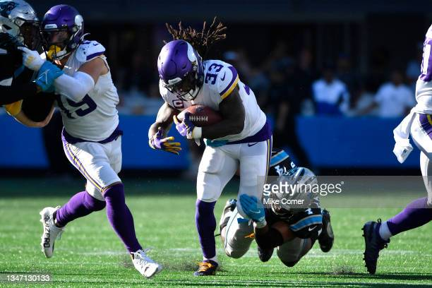 Jermaine Carter Jr. #4 of the Carolina Panthers tackles Dalvin Cook of the Minnesota Vikings during the fourth quarter at Bank of America Stadium on...
