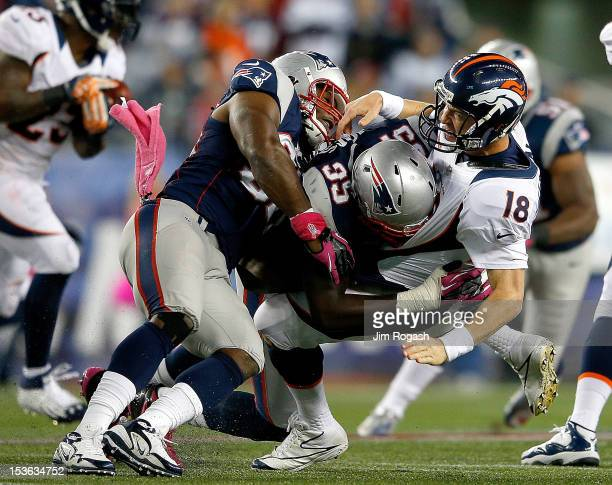 Jermaine Cunningham and Chandler Jones of the New England Patriots rough up Peyton Manning of the Denver Broncos after he released a pass during the...