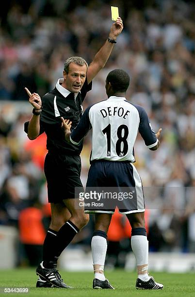 Jermaine Defoe of Tottenham is booked by referee Martin Atkinson after celebrating scoring the first goal with the crowd during the Barclays...