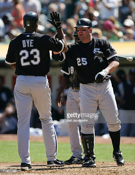 Jermaine Dye of the Chicago White Sox is congratulated by Jim Thome after hitting a two run home run in the third inning against the Oakland...