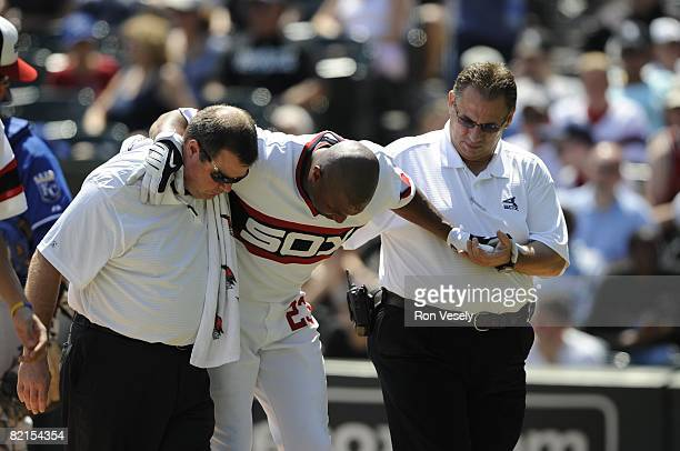 Jermaine Dye of the Chicago White Sox is helped off the field by assistant trainer Brian Ball and head trainer Herm Schneider after being hit in the...