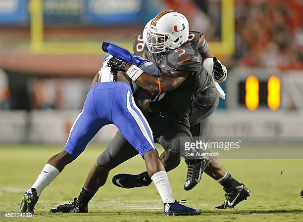Jermaine Grace of the Miami Hurricanes tackles Shaun Wilson of the Duke Blue Devils on September 27 2014 at Sun Life Stadium in Miami Gardens Florida