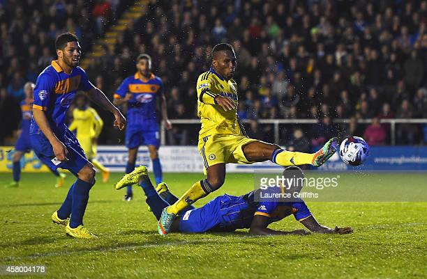 Jermaine Grandison of Shrewsbury Town heads the ball clear of Didier Drogba of Chelsea to score an own goal during the Capital One Cup Fourth Round...