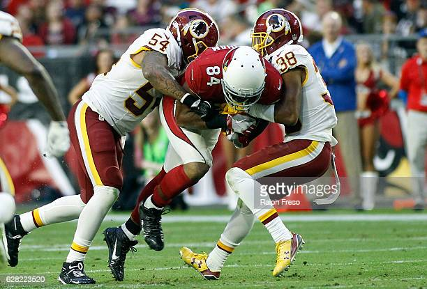 Jermaine Gresham of the Arizona Cardinals is tackled by Mason Foster and Kendall Fuller of the Washington Redskins after a catch during the fourth...