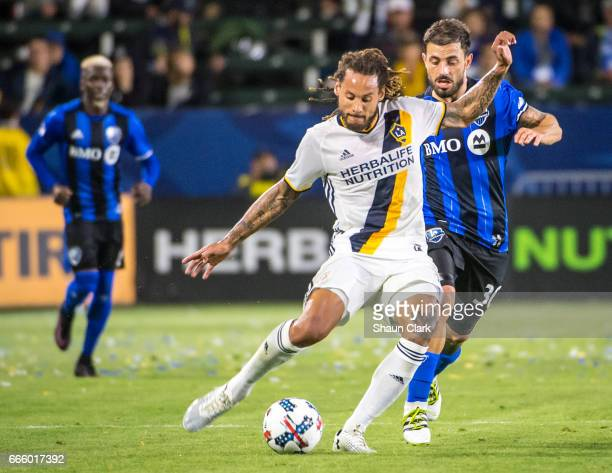 Jermaine Jones of Los Angeles Galaxy crosses the ball as Hernan Bernardello of Montreal Impact defends during Los Angeles Galaxy's MLS match against...
