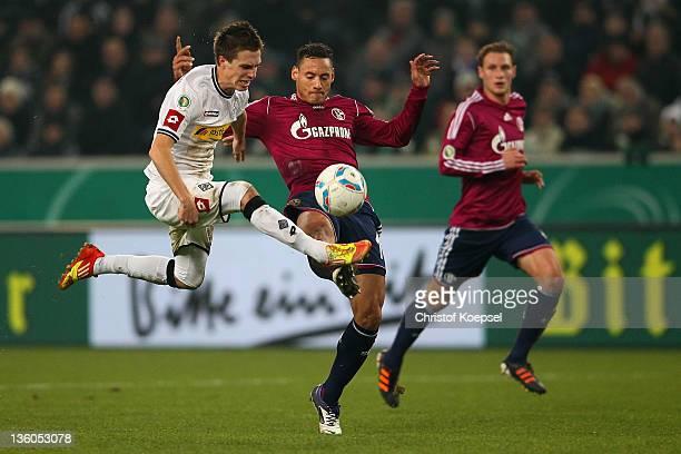 Jermaine Jones of Schalke challenges Patrick Herrmann of Moenchengladbach during the DFB Cup round of sixteen match between Borussia Moenchengladbach...
