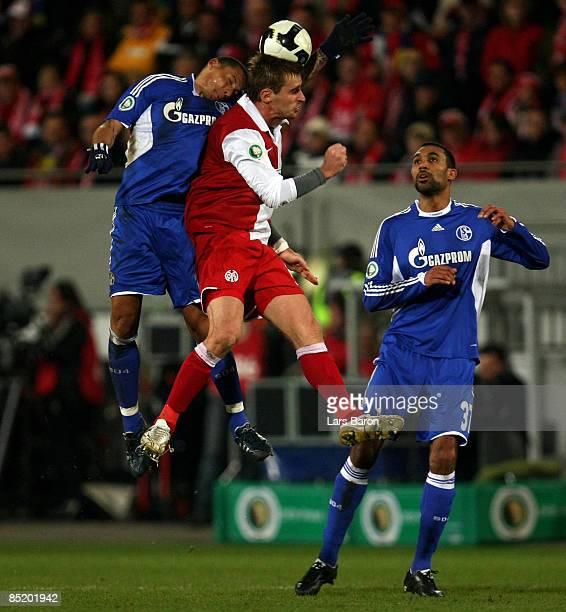 Jermaine Jones of Schalke goes up for a header with Milorad Pekovic of Mainz in front of Orlando Engelaar of Schalke during the DFB Cup quarter final...