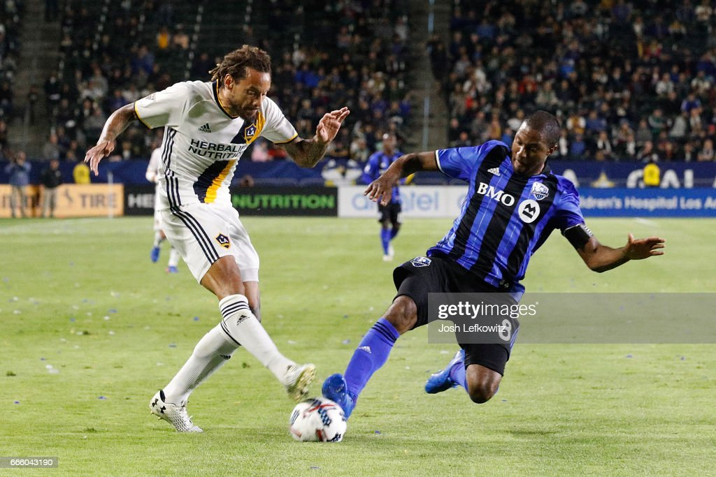 Jermaine Jones #13 of the Los Angeles Galaxy attempts to kick the ball while Patrice Bernier #8 of the Montreal Impact slides into play during the Los Angeles Galaxy's MLS match against the Montreal Impact at the StubHub Center on April 7, 2017 in Carson, California.