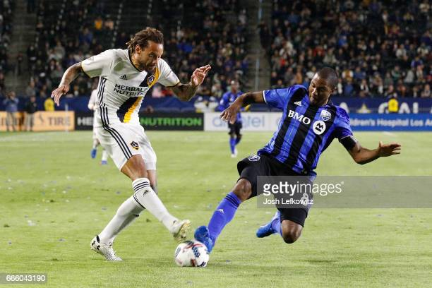 Jermaine Jones of the Los Angeles Galaxy attempts to kick the ball while Patrice Bernier of the Montreal Impact slides into play during the Los...
