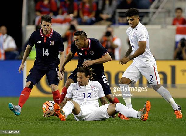 Jermaine Jones of the United States falls to the ground battling for the ball against David Guzman of Costa Rica during the first half at Red Bull...