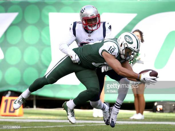 Jermaine Kearse of the New York Jets dives forward past Jonathan Jones of the New England Patriots for a first quarter touchdown at MetLife Stadium...