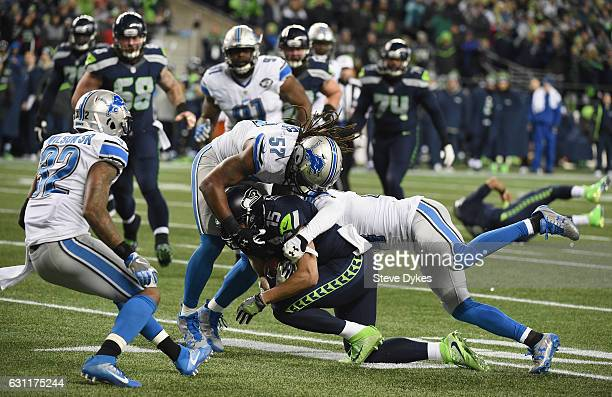 Jermaine Kearse of the Seattle Seahawks is tackled by Josh Bynes and Nevin Lawson of the Detroit Lions during the first half of the NFC Wild Card...