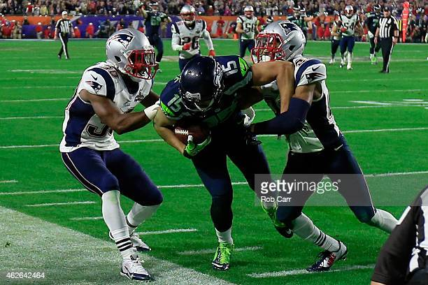 Jermaine Kearse of the Seattle Seahawks makes a catch against Malcolm Butler and Duron Harmon of the New England Patriots in the fourth quarter...