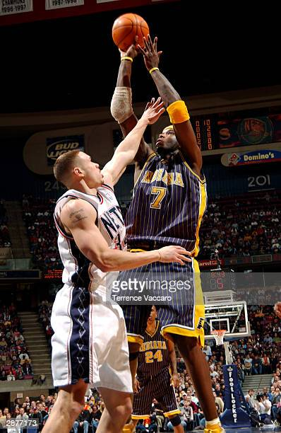 Jermaine O'Neal of the Indiana Pacers attempts a jump shot against Aaron Williams of the New Jersey Nets at Continental Airlines Arena January 17...