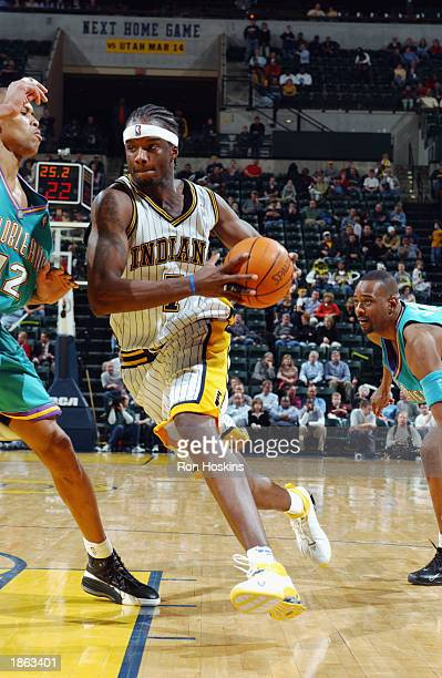 Jermaine O'Neal of the Indiana Pacers drives against PJ Brown of the New Orleans Hornets during the game at Conseco Fieldhouse on March 11 2003 in...