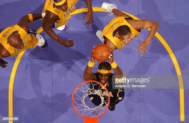 Jermaine O'Neal of the Indiana Pacers dunks against Brian Cook of the Los Angeles Lakers on January 9 2006 at Staples Center in Los Angeles...