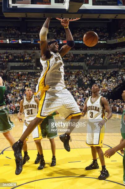 Jermaine O'Neal of the Indiana Pacers jams on the Boston Celtics while teammates Al Harrington and Reggie Miller look on during game one of the...