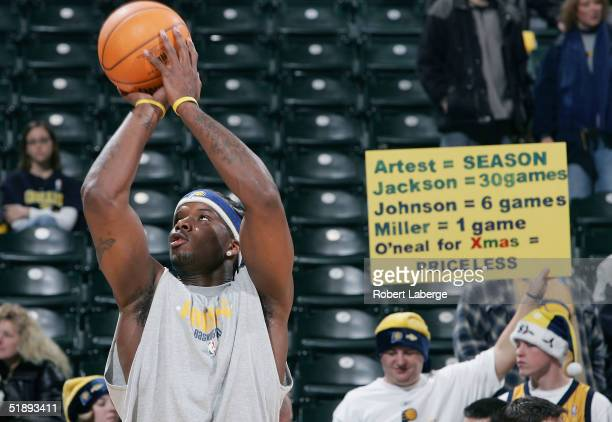 Jermaine O'Neal of the Indiana Pacers warms up before the game against the Detroit Pistons as a fan holds a sign welcoming O'Neal back for his first...