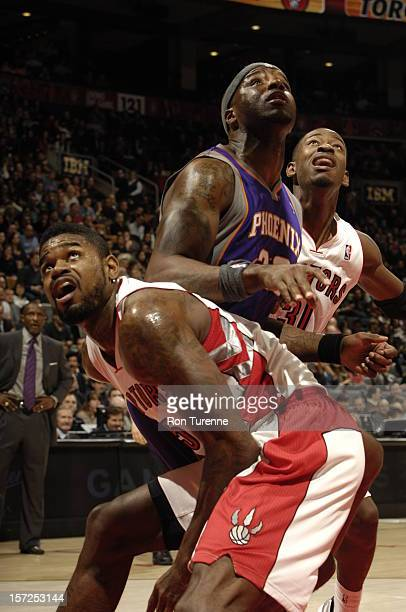 Jermaine O'Neal of the Phoenix Suns battles for positioning against Amir Johnson and Terrence Ross of the Toronto Raptors on November 30 2012 at the...