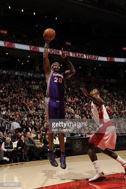Jermaine O'Neal of the Phoenix Suns shoots the ball against Amir Johnson of the Toronto Raptors on November 30 2012 at the Air Canada Centre in...