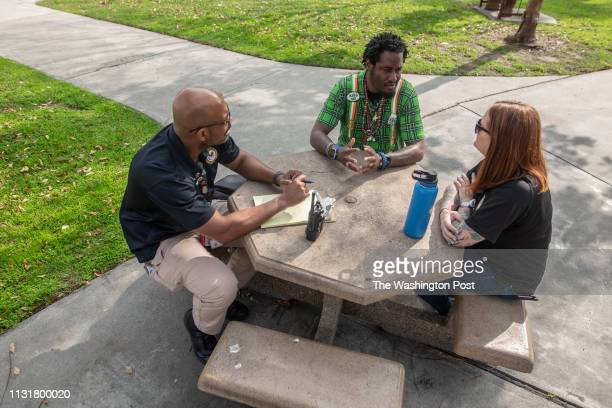 Jermaine Petit talks with Tyrone Anderson and Shannon Teague of the Veterans Crisis Response Team outside of the Veterans Administration Hospital in...