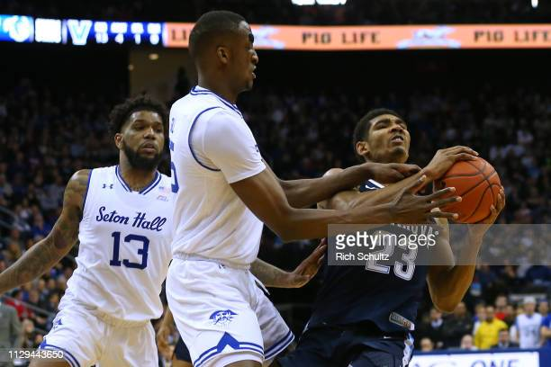 Jermaine Samuels of the Villanova Wildcats fights off Myles Powell and Romaro Gill of the Seton Hall Pirates during the first half of a college...