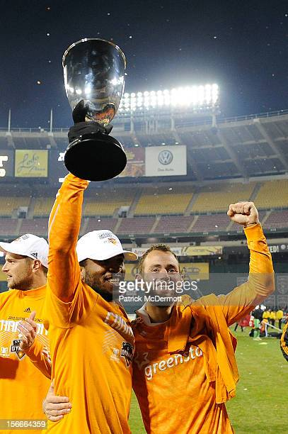 Jermaine Taylor and Brad Davis of Houston Dynamo celebrate with the MLS 2012 Eastern Conference Championship trophy after defeating DC United on an...