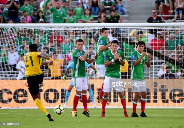 Jermaine Taylor of Jamaica attempts a shot on a free kick around Erick Torres Jesus Duenas Jesus Molina and Erick Gutierrez of Mexico during the...