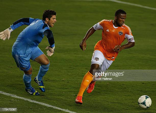 Jermaine Taylor of the Houston Dynamo fights for the ball against Matt Lampson of the Columbus Crew at BBVA Compass Stadium on August 3 2013 in...