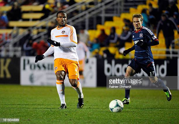 Jermaine Taylor of the Houston Dynamo makes a pass as Chris Rolfe of the Chicago Fire defends during the first half of their game at Blackbaud...