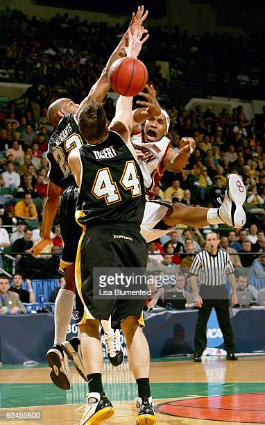 Jermaine Watson of the Boston College Eagles passes under pressure from Adrian Tigert and Ed McCants of the WisconsinMilwaukee Panthers during the...