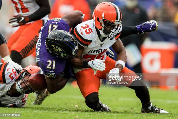 Jermaine Whitehead of the Cleveland Browns causes a fumble against Mark Ingram of the Baltimore Ravens during the second half at MT Bank Stadium on...
