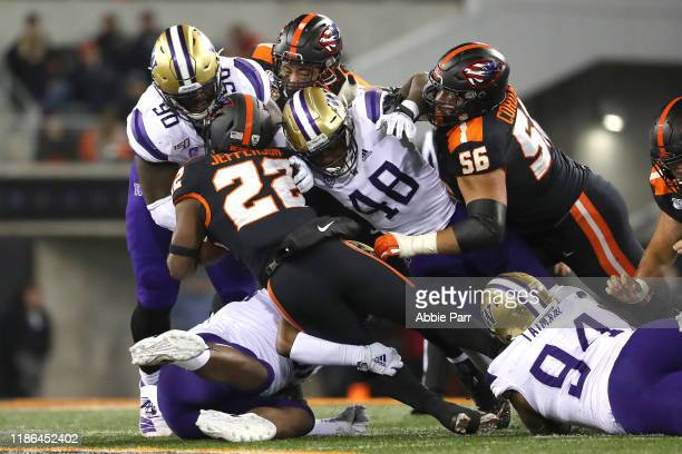 Jermar Jefferson of the Oregon State Beavers is tackled by the Washington Huskies in the fourth quarter during their game at Reser Stadium on...