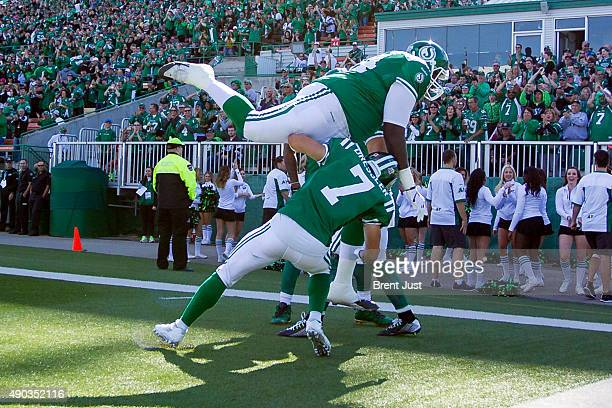 Jermarcus Hardrick and Weston Dressler of the Saskatchewan Roughriders celebrate with teammates after touchdown in the game between the Montreal...