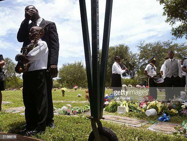 Jermel Stuart holds his grandfather Thomas Cash's saxophone at the grave site of the former leader of the Progressive Coronet Marching Band July 12,...