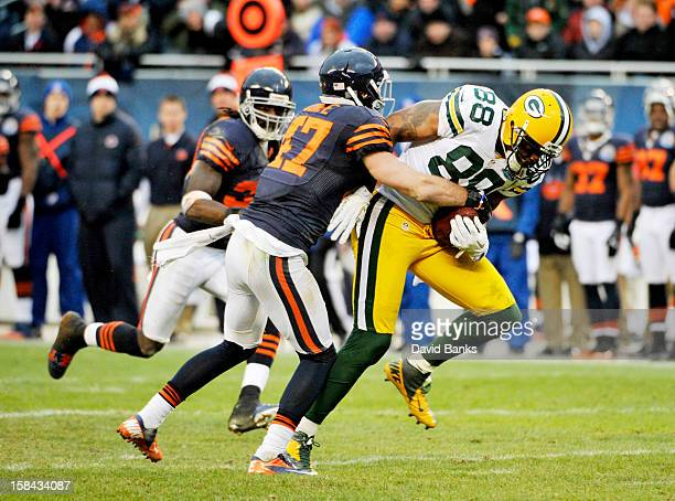 Jermichael Finley of the Green Bay Packers catches a pass and is tackled by Chris Conte of the Chicago Bearson December 16 2012 at Soldier Field in...