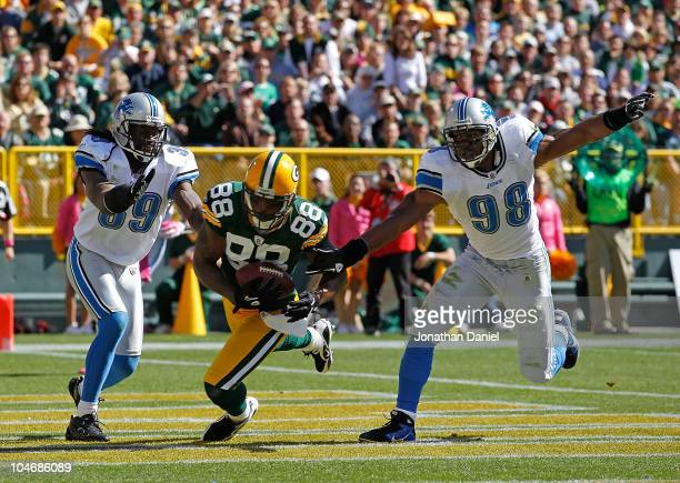 Jermichael Finley of the Green Bay Packers catches a touchdown pass between CC Brown and Julian Peterson of the Detroit Lions at Lambeau Field on...
