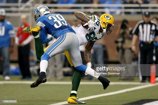 Jermichael Finley of the Green Bay Packers crosses the goal line against Ricardo Silva of the Detroit Lions at Ford Field on November 18, 2012 in...