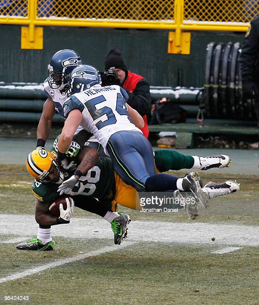 Jermichael Finley of the Green Bay Packers leaps for a first down as he is hit by Deon Grant and Will Herring of the Seattle Seahawks at Lambeau...