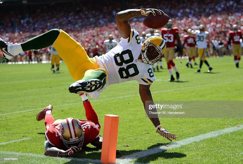 Jermichael Finley #88 of the Green Bay Packers scores on a twelve yard pass play diving over the tackle of Donte Whitner #31 of the San Francisco 49ers during the second quarter at Candlestick Park on September 8, 2013 in San Francisco, California.