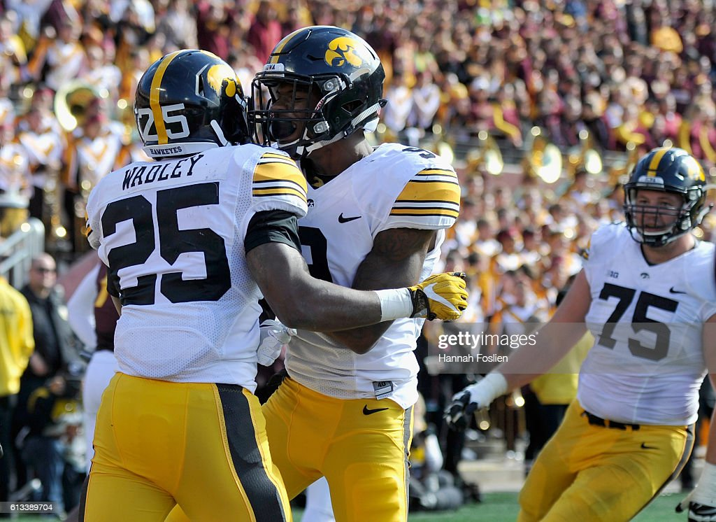 Jerminic Smith #9 of Iowa congratulates teammate Akrum Wadley #25 on a touchdown against Minnesota during the fourth quarter of the game on October 8, 2016 at TCF Bank Stadium in Minneapolis, Minnesota. Iowa defeated Minnesota 14-7.
