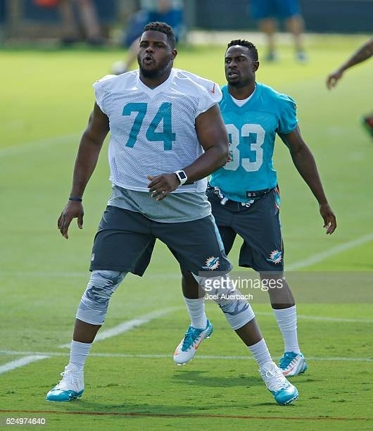 Jermon Bushrod and Ifo EkpreOlomu of the Miami Dolphins warm up prior to the team's voluntary veterans minicamp on April 27 2016 at the Miami...
